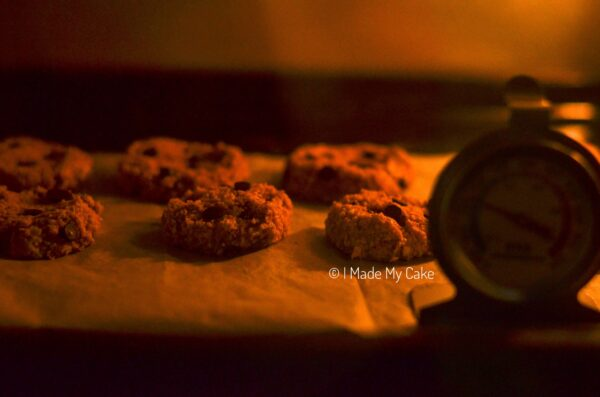 banana oatmeal chocolate chip cookies baking in the oven with an oven thermometer