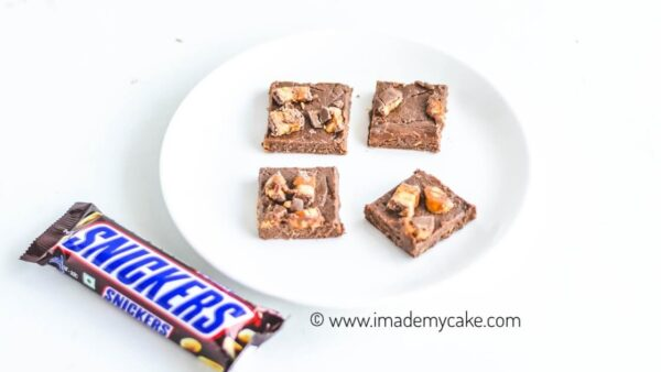 four snickers fudge slices on a white plate